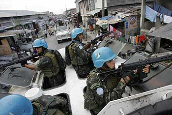 Brazilian U.N. peacekeepers ride an armored personnel carrier on the main road of the Cite Militaire district of Port-au-Prince, Haiti, in February 2006, as part of their efforts to curtail violence blamed on armed gangs in the bordering shantytown of Cite Soleil. (Photo: Roberto Schmidt / AFP-Getty Images)